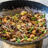 Красный рис с овощами и креветками, приготовленный в воке