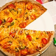 Пицца с сыровяленой говядиной и куриной грудкой, помидорами и зеленью.